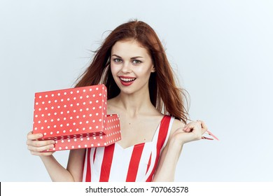 Woman with a smile with a gift box on a light background