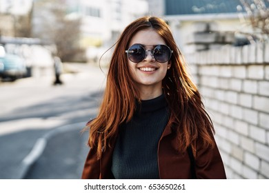 Woman with a smile, woman with glasses on a brick wall background
