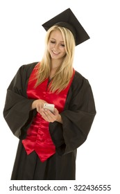a woman with a smile graduating and looking down at her cell phone.