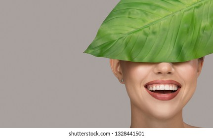 Woman smile and green leaf. Organic beauty. Gray background.