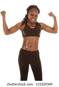 A woman with a smile on her face flexing her arms
