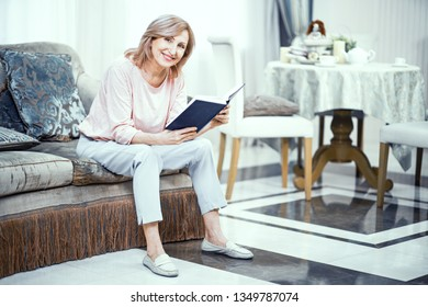 A Woman With a Smile on Her Face is Reading a Book While Sitting on the Sofa. A Woman Looks Older Than 50 Years. She is Dressed in Home Clothes in Her Living Room.