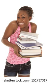 a woman with a smile on her face holding on to a stack of books.