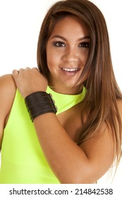 A woman with a smile on her face, wearing a leather bracelet and lime green top.