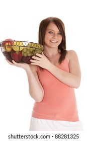 A woman with  a smile on her face holding a fruit bowl.