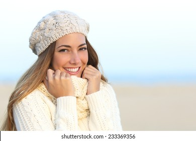 Woman smile with a perfect white teeth in winter with the beach in the background