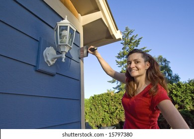 Woman smiles with her hand on her hip as she paints her house. Horizontally framed photograph.