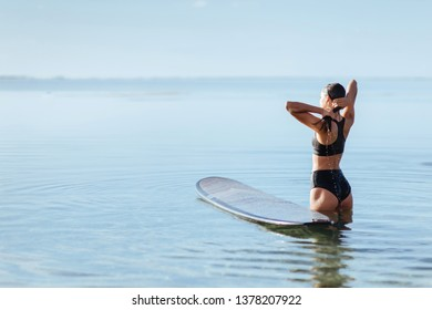 Woman smiles and sits on the surfboard in the ocean. summertaime.