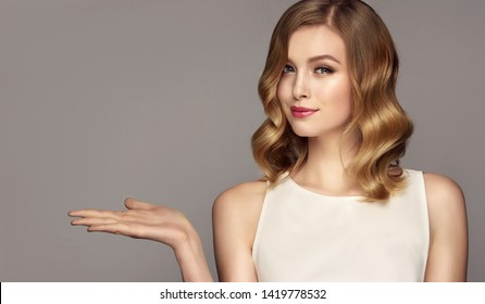 Woman  smiles surprise showing product .Beautiful girl with curly hair pointing to the side . Presenting your advertisement. Expressive facial expressions