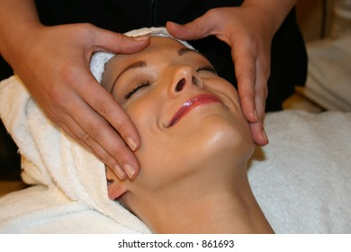 Woman Smiles While receiving Facial Massage
