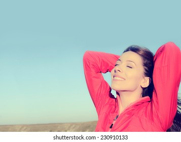 Woman smiling arms raised up to blue sky, celebrating freedom. Positive human emotions, face expression feeling life perception success, peace of mind concept. Free Happy girl on beach enjoying nature