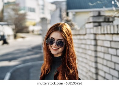 Woman smiling at the background of a brick fence