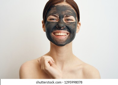 woman smiling in a cosmetic mask made of clay lifting