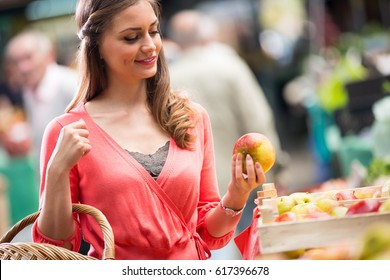 woman smiling with green apples at market store