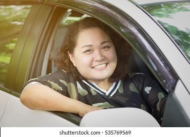 Woman smiling greetings in car.