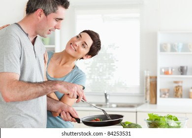 Woman smiling at her pan-holding husband in a kitchen
