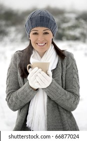 Woman smiling holding hot drink outside in the snow