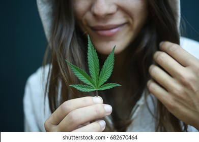 woman smiling holding a marijuana leaf