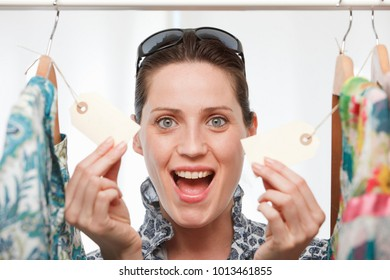 woman smiling holding price tags
