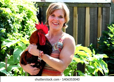 Woman smiling holding a rooster in her arms while in a garden in front of a fence.
