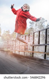 Woman smiling and jumping on a bridge.