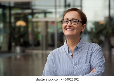 Woman smiling looking at the camera. Happy and successful business woman in the office. Middle-aged mature brunette 40, 50 years old wearing glasses. Portrait of secretary,agent, teacher, manager, ceo