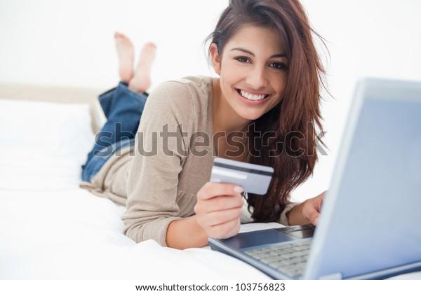 Eine Frau lächelt und sieht vor ihr, wie sie ihre Kreditkarte mit ihrem Laptop benutzt.