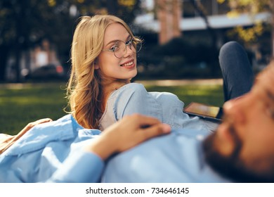 woman smiling, man with beard, business partners lying on grass in park