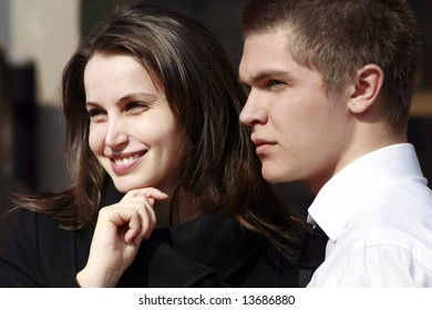 woman smiling and man profile looking far away outdoors