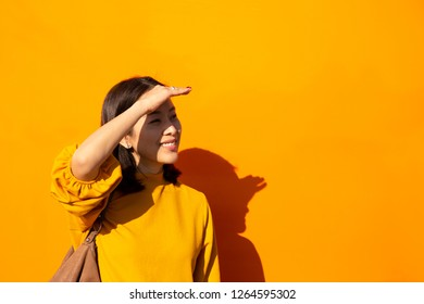 Woman smiling in orange top with hand on forehead in orange background.