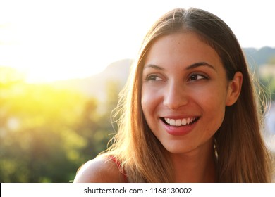 Woman smiling with perfect smile and white teeth thinking and looking sideways in park in summer. Sunlight flare. Copy space.