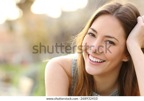 公園やカメラを見ながら完璧な笑顔と白い歯を持つ女性