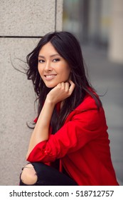 Woman smiling - portrait of happy lovely and beautiful mixed race Asian Caucasian young businesswoman in casual clothes outdoor sitting on steps
