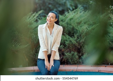 Woman smiling - portrait of happy lovely and beautiful mixed race Asian Caucasian young businesswoman in casual clothes outdoor sitting in park