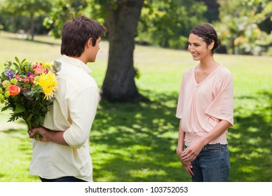 Woman smiling as she greets her friend who is holding flowers behind his back