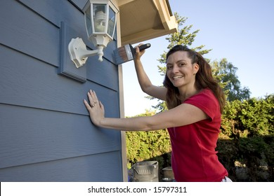 Woman smiling as she paints a house. Horizontally framed photograph.