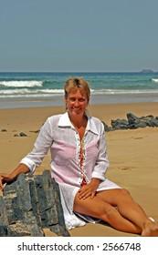 Woman smiling sitting in the sand on the beach