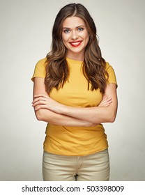 Woman smiling with teeth standing against isolated background with crossed arms.