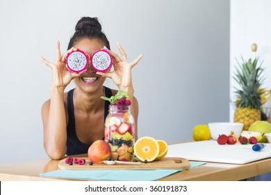 Mulher sorrindo com uma salada de frutas tropicais, sendo brincalhão cobrindo seus olhos com frutas de dragão