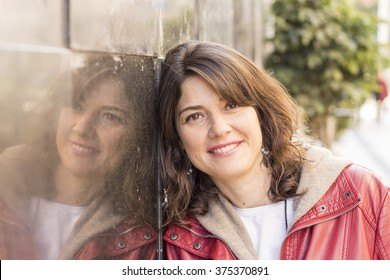 Woman smiling while leaning on wall outdoors