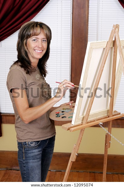 a woman smiling while painting a picture on her blank white canvas