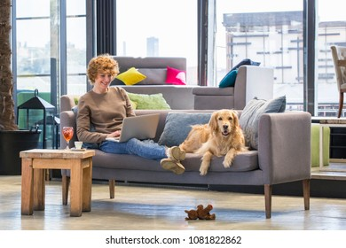 Woman smiling and working on laptop while her dog lying next to her