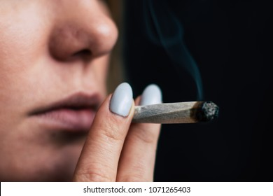 A woman smokes cannabis weed, a joint and a lighter in his hands. Smoke on a black background. Concepts of medical marijuana use and legalization of the cannabis. On a black background