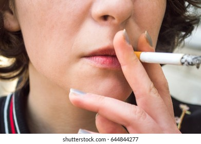 A woman smokes in the street. Close up