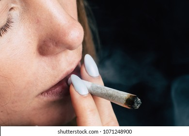 A woman smokes weed cannabis a joint and a lighter in his hands. Smoke on a black background. Concepts of medical marijuana use and legalization of the cannabis. On a black background