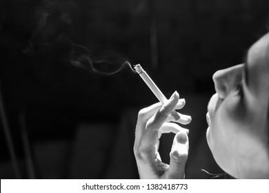Woman smoking a cigarette. Cigarette smoke spread. Black and white photo