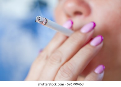 Woman smoking a cigarette. Smoke spread.
