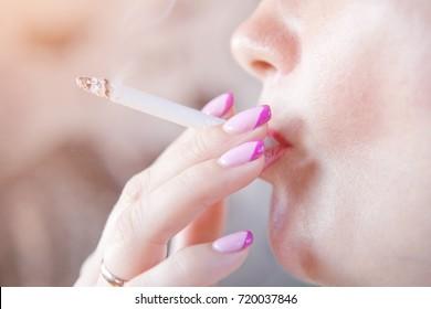 Woman smoking a cigarette. Cigarette smoke spread.