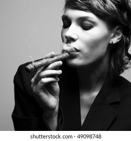Woman smoking cigars. Studio fashion photo