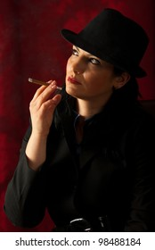 Woman smoking in darkness and looking away to the light
